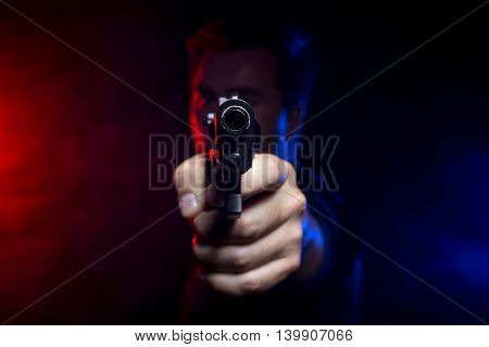 Cop shooting a criminal or terrorist with gun smoke lit by police lights