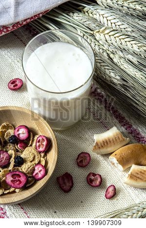 Milk drink in a glass, bagels and granola on the table