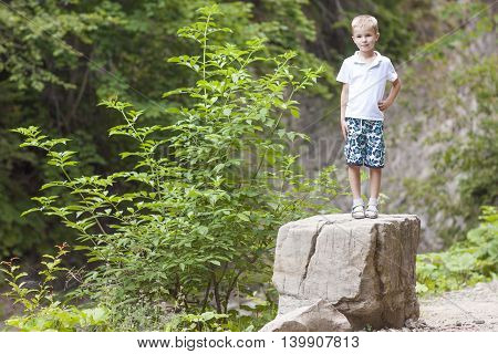 Little smiling boy standing on a big stone