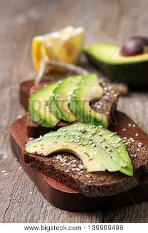 toast with slices of avocado and spices sesame seeds on a wooden background