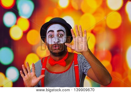 Pantomime man with facial paint posing for camera interacting funny using hands, blurry lights background.