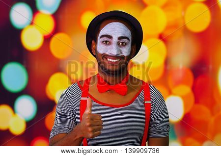 Pantomime man with facial paint posing for camera interacting giving thumbs up smiling, blurry lights background.