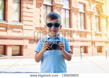 Smiling small boy in sunglasses is holding a camera ready to take a shot on the background of old building on a sunny day