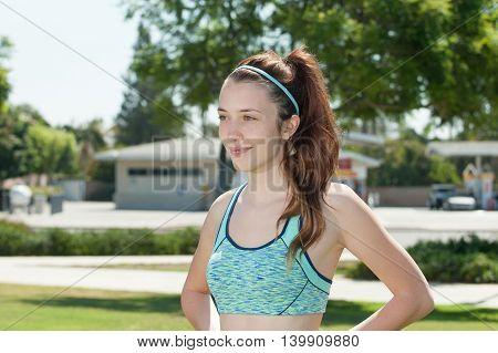 Landscape view of pretty teen athlete half body looking forward.