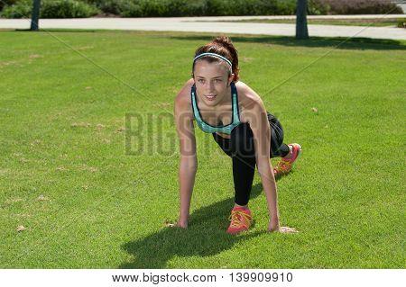 Flexible female athlete stretching her hip flexor facing forward.