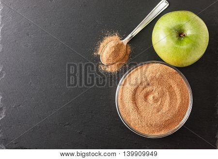 crushed apple fiber apple green on a black background with space for text (top view). dietary product