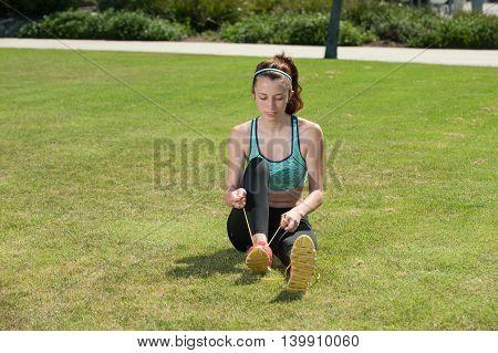 Beautiful teen girl tying her shoe before workout.