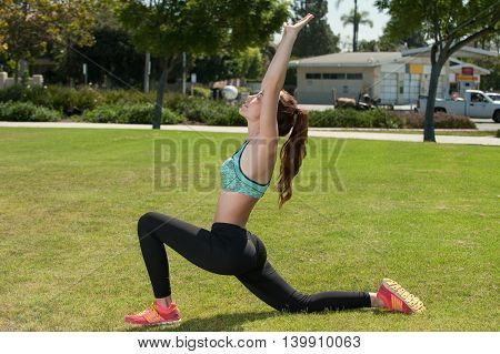 Flexible female athlete stretching her hip flexor while reaching up.