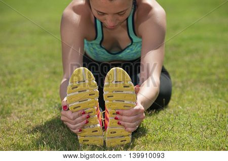 Female teenage runner stretching to grab her soles in close view.