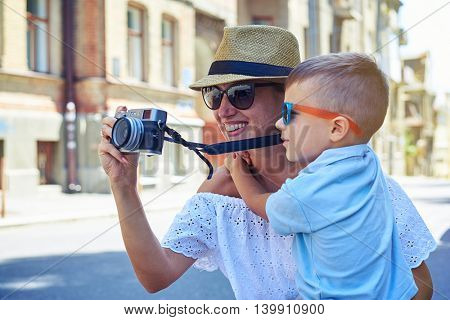 Close-up of young smiling woman with her small son who is taking a photo during their walk in the city on a sunny summer day