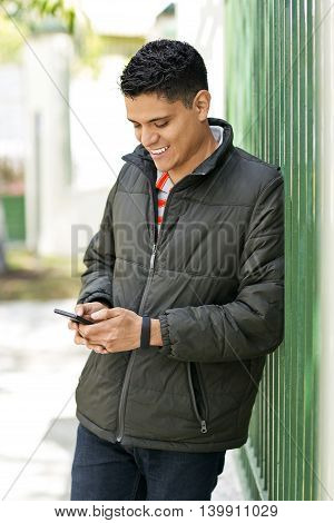 Latin young man smiling outdoors with smartphone