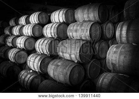 Wine barrels stacked in the old cellar of the winery. Black and white
