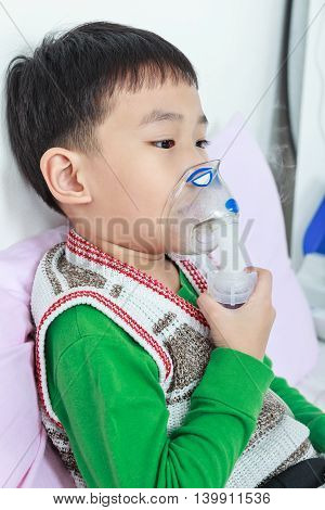Asian Child Holds A Mask Vapor Inhaler For Treatment Of Asthma. Breathing Through A Steam Nebulizer.