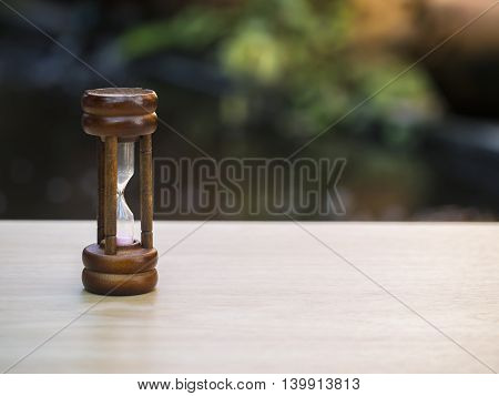Hourglass on blurred natural background, select focus