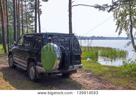 The river Berd Novosibirsk oblast Siberia Russia - July 25 2016: a fisherman with a car (SUV) on the banks of the river