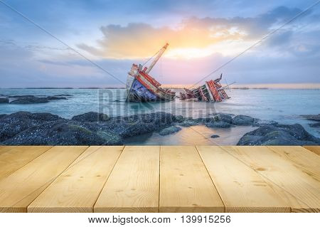 Ancient shipwrecks in the sea with sunset background.