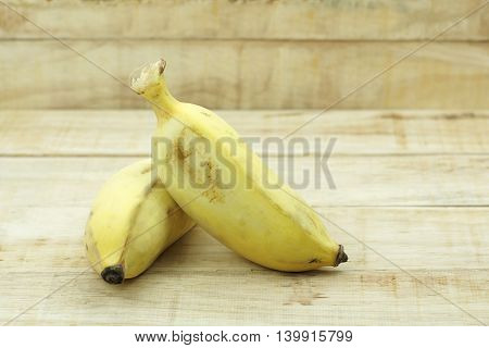 Stack of Asian yellow banana on wood background. Thai name Klay Nam Wa.