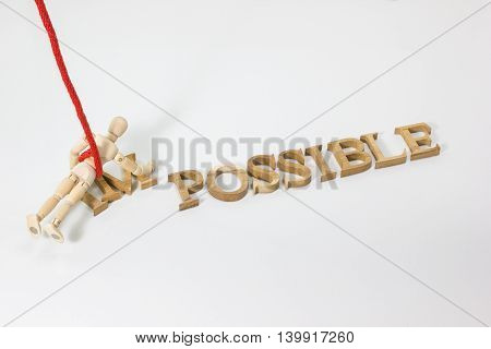 Changing the word impossible to possible with wooden dummy hanging on the red rope