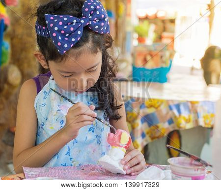 Cute Asian Girl Painting Color On The Plaster Statue.