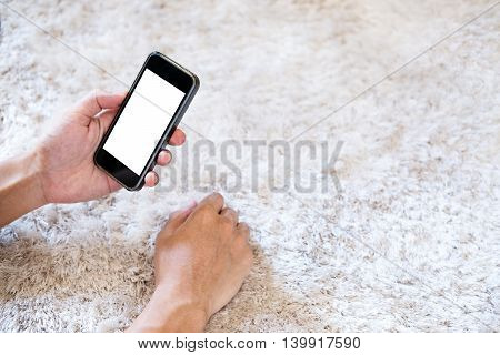Hand using smart phone on white carpet, selective focus