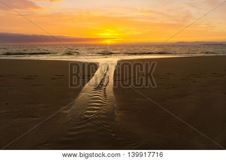Ocean sunset is a sandy beach scenic with a soft flowing stream and a vivid vibrant sunset sky on the horizon.oceansunset