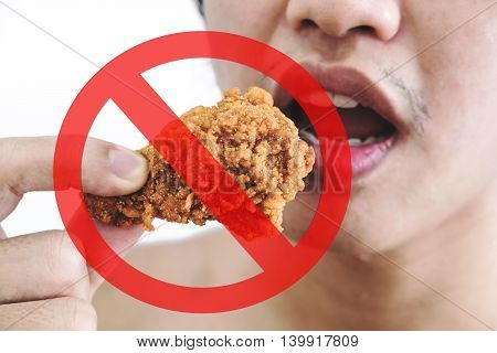 Asian guy biting fried chicken with danger label, concept of dieting and danger of fastfood