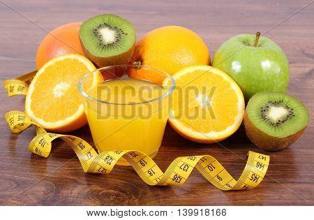 Fresh ripe fruits glass of juice and tape measure on board grapefruit orange kiwi apple healthy lifestyles nutrition and strengthening immunity
