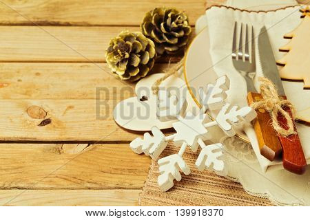 Christmas retro table setting with wooden ornaments plate fork and knife