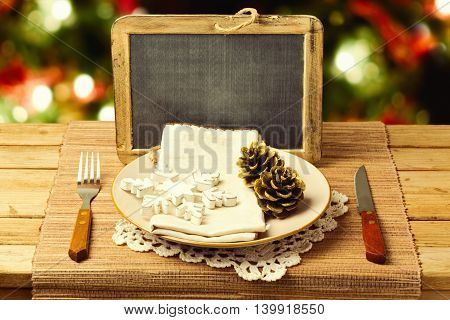 Christmas table setting with plate fork knife ornaments and chalkboard on wooden table