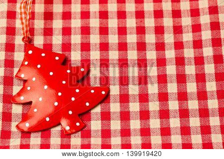 Christmas tree ornament on red checked tablecloth