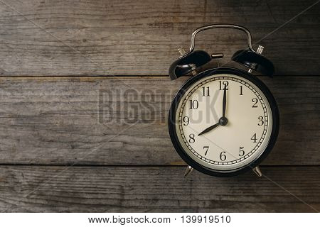 Retro alarm clock on wooden table, conceptual of time
