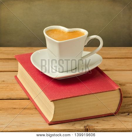 Coffee cup on book. Heart shape cup symbol of love