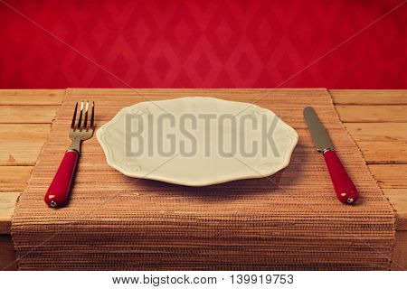Empty plate with knofe and fork on placemat over red wallpaper background