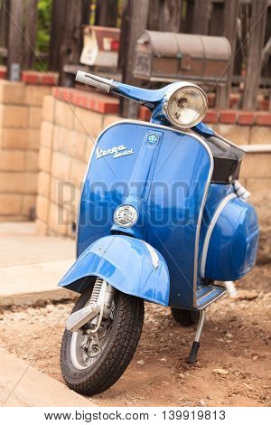 Laguna Beach, CA, USA - July 23, 2016: Blue retro Vespa moped parked in front of a home in Laguna Beach, California, United States in summer. Editorial use only.