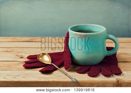 Cup of tea with lipstick stain and wool gloves on wooden table