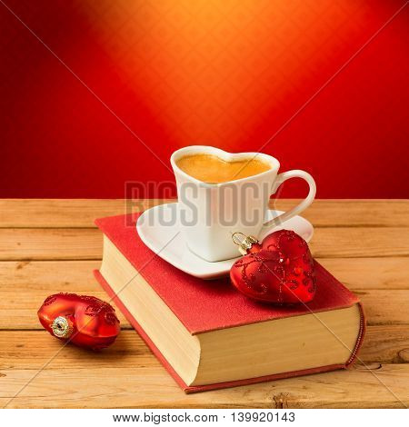 Coffee cup on book with Christmas decorations. Heart shape cup and ornaments.