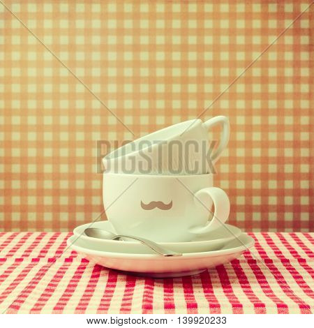 Coffee cups with hipster mustache on checked tablecloth