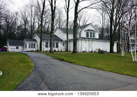 WEQUENTONSING, MICHIGAN / UNITED STATES - DECEMBER 23, 2015: The front porch of a white home with a long driveway, on Beach Drive in Wequetonsing, is protected from the winter weather.