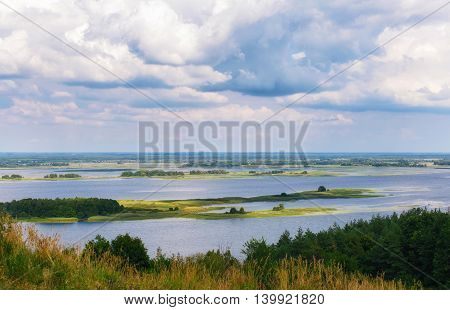 Beautiful summer landscape with river and blue sky with clouds in Village Vitachev Ukraine. The view from the mountains to the river Dnepr