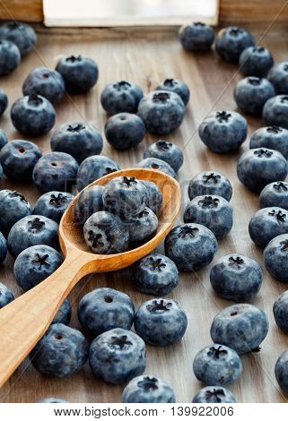 Blueberries and wooden spoon on a wooden background