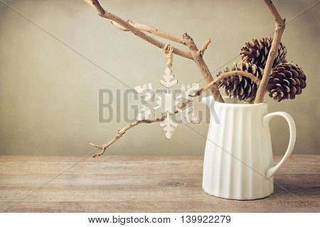Winter branches with Christmas decoration in white jug