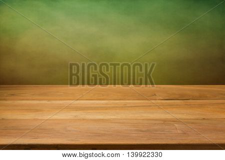 Kitchen wooden table over green grunge background
