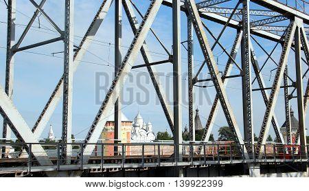 Railway metal bridge perspective view. Russian monastery on backdrop