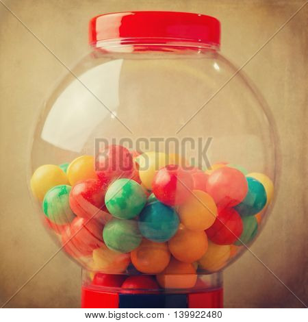 Gumball machine detail with colored balls over grunge background