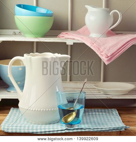 Shabby chic retro style kitchen tableware on wooden stand