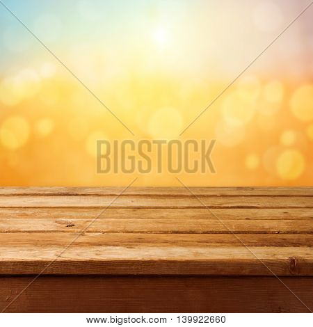 Empty wooden deck table over sunset bokeh background