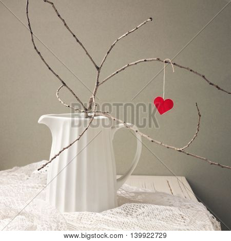Paper heart hanging on tree branch. Valentine's Day concept.