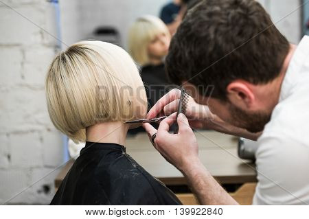 Hairdresser cutting client's hair in salon with electric razor closeup