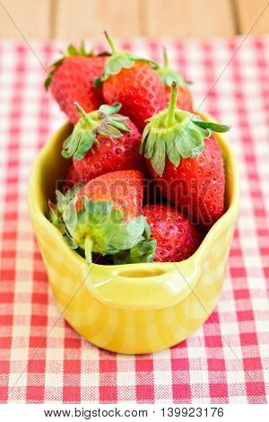 Fresh red strawberry fruit on checked tablecloth