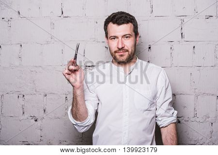 Portrait of young beautiful hairdresser man wearing white shirt with scissors ongrey brick wall.